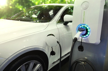 Power supply connect to electric vehicle or EV car for charge to the battery. Charging technology industry transport in Eco-friendly alternative energy concept to green energy.