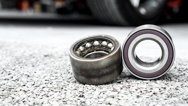 New wheels car bearing and old wheels car bearing on asphalt floor in garage and copyspace