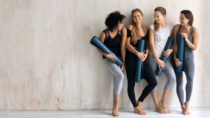 Beautiful diverse girls with yoga mats chatting and laughing