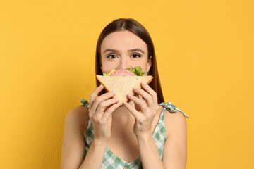 Young woman eating tasty sandwich on yellow background
