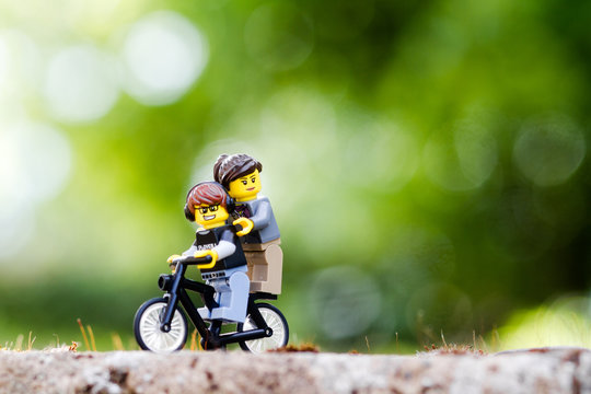 Orvieto, Italy - August 16th 2015: Couple of Lego minifigure on bike in sunset. Lego is a popular line of construction toys manufactured by the Lego Group