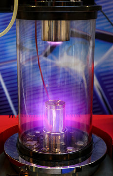 Mangetron sputtering with purple glowing plasma in vacuum glass tube