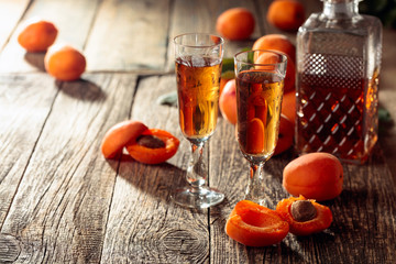 Apricot liquor and fresh apricots on a old wooden table.