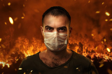Foto auf AluDibond Violett rot A man in a medical mask to protect the cuts of breath against the backdrop of severe forest fires. The concept of fires in Australia.