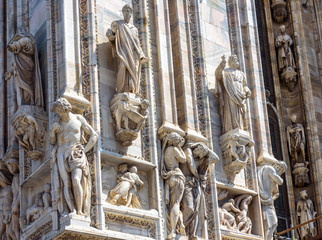 Milan Cathedral (Duomo di Milano) close-up, Milan, Italy. Detail of luxury facade with many marble statues and reliefs.
