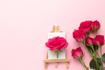 Canvas for painting with roses flower on pink background with copyspace , spring and creativity concept