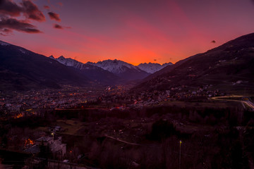 Wall Murals Crimson Panorama of Aosta city at sunset, with mountains on background and colorfull sky