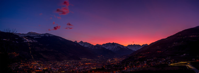 Papiers peints Aubergine Panorama of Aosta city at sunset, with mountains on background and colorfull sky