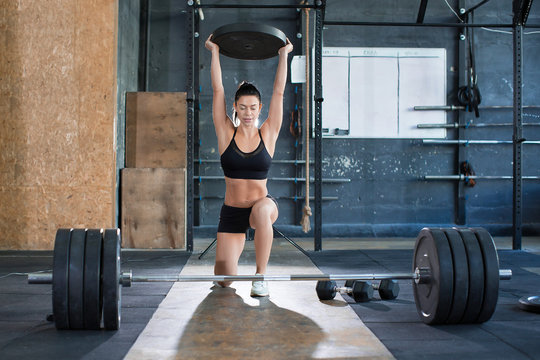 Close up front portriat of a woman is lifting weight while working out in gym. Exercise for legs. Healthy lifestyle concept.