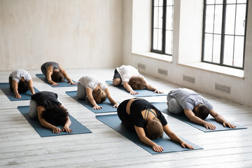 Diverse young people relaxing in Child pose, practicing yoga