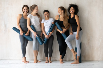 Happy beautiful diverse girls with yoga mats standing in gym