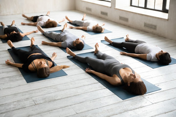 Diverse sporty people practicing yoga, relaxing in Savasana exercise