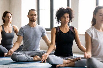 Diverse young people meditating, sitting in Lotus pose, practicing yoga