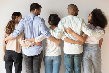Back view of happy international young people stand hugging