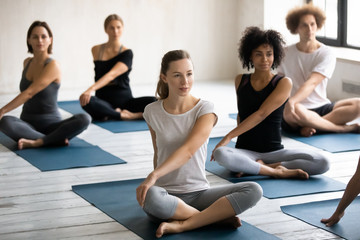 Diverse young people practicing yoga, doing Parivritta Sukhasana exercise
