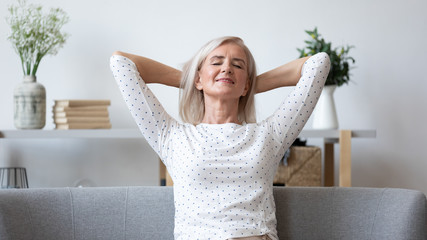 Happy elderly woman relax on sofa at home