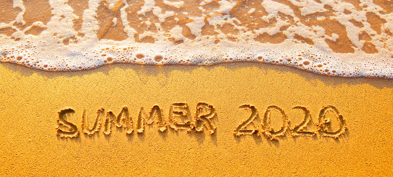 Background with text Summer 2020 on sandy beach