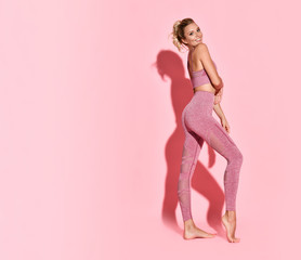 studio photo of sexy sporty woman with nice fitness body over pink background