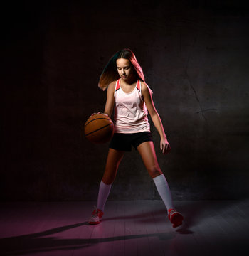 Teenage Girl dribbling basketball