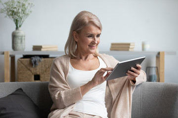 Elderly woman relax at home using electronic tablet