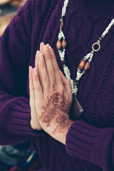 woman hands in namaste mudra gesture  with henna drowing on hands outdoor shot