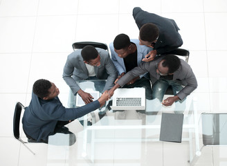 top view. business colleagues shaking hands during office meeting.