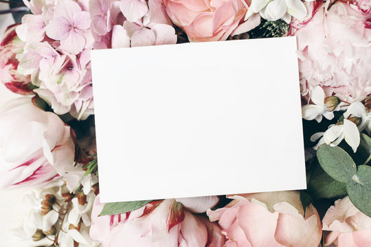 Wedding, birthday stationery mock-up scene. Blank paper greeting card, invitation. Decorative floral composition. Closeup of pink roses petals, peonies, hydrangea flowers and eucalyptus leaves.