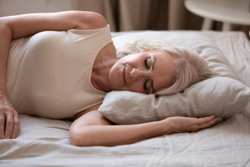 Calm senior woman sleeping in comfortable bed at home
