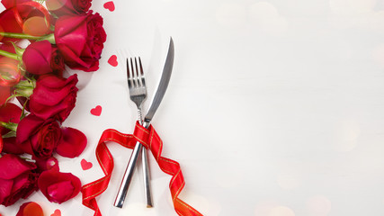 Celebration food background. Cutlery and roses on white table