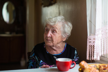 An elderly old woman in the kitchen sitting at the table.