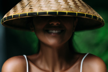 Portrait of a beautiful girl in an Asian conical hat. Portrait of a smiling girl. Beautiful smile. Close-up smile. Funny girl. Smiling girl. Funny portrait. A woman in a Balinese conical hat.
