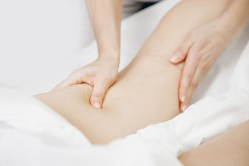 Anti-cellulite massage treatment on legs of young women beauty spa