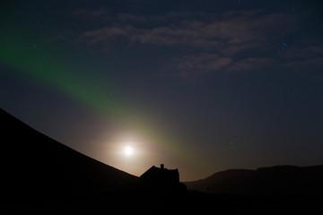 unbewohntes , dunkles, mystisches Haus vor Hügeln mit Polarlicht