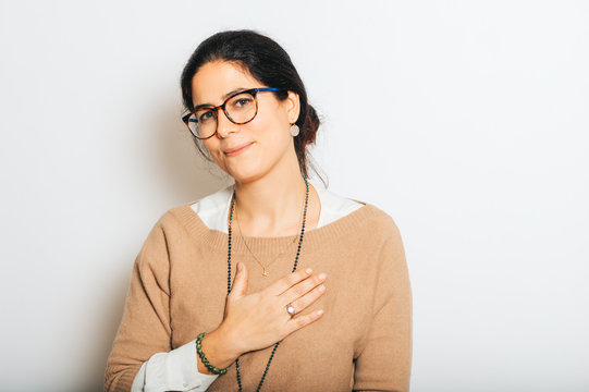Studio portrait of beautiful brunette woman, wearing glasses, showing thank you gesture, posing on white background