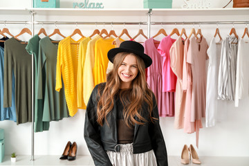 Beautiful young woman in shop with modern clothes