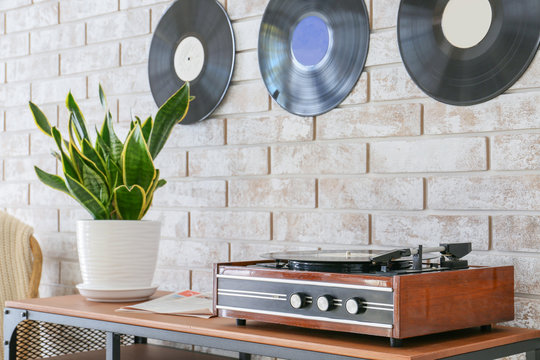 Record player with vinyl disc on table in room