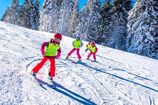 Group of kids learning how to ski on slope in mountains during winter vacation