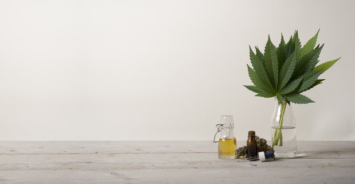 banner showing CBD oil in glass bottle, Cannabis sativa marijuana weed leaves and dropper bottle, on industrial wooden ground floor