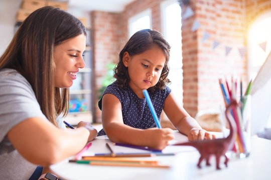 Beautiful teacher and toddler girl drawing draw using colored pencils at kindergarten