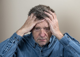 Head and shoulders portrait of a senior caucasian man with head in hands and looking depressed