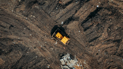 Aerial top view of a construction site or country dump with yellow excavator or bulldozer, heavy equipment, drone photo.