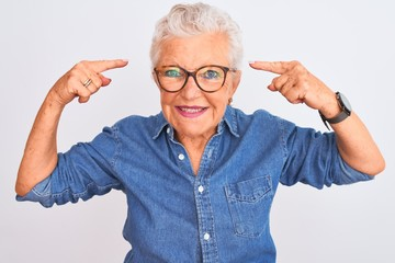 Senior grey-haired woman wearing denim shirt and glasses over isolated white background smiling pointing to head with both hands finger, great idea or thought, good memory Wall mural