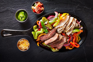 Wall Mural - aerial view of a iron skillet filled with steak and chicken mexican fajitas on slate