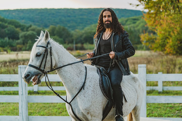 Handsome rider man on horse. Equestrian rides his white well looking horse. Handsome man riding horse at farm. Attractive male sitting on white stallion on the ranch in autumn. Wall mural