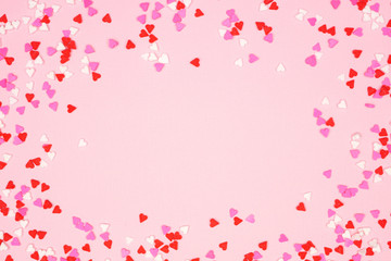 Wall Mural - Valentines Day frame of candy heart sprinkles over a pink textured background. Copy space.