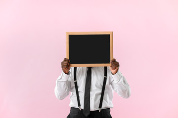 African-American teacher with chalkboard on color background