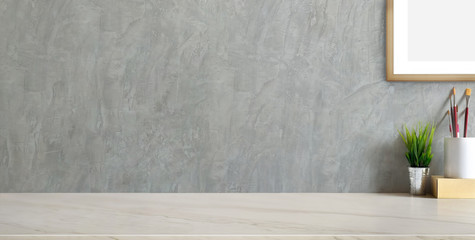 Wall Mural - Cropped shot of trendy workplace with copy space and office supplies on marble background and loft grey wall
