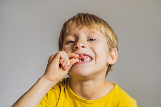 Litle caucasian boy holds a dropped milk tooth between his fingers and laughs looking into the camera
