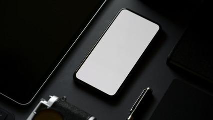 Obraz Cropped shot of blank screen smartphone in dark modern office - fototapety do salonu