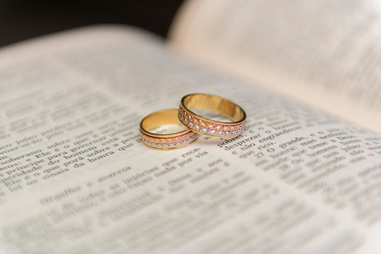 "Wedding rings on a holy bible ""Bíblia Sagrada"". Concept of union, love, companionship, faithfulness. Religious union. Selective focus."
